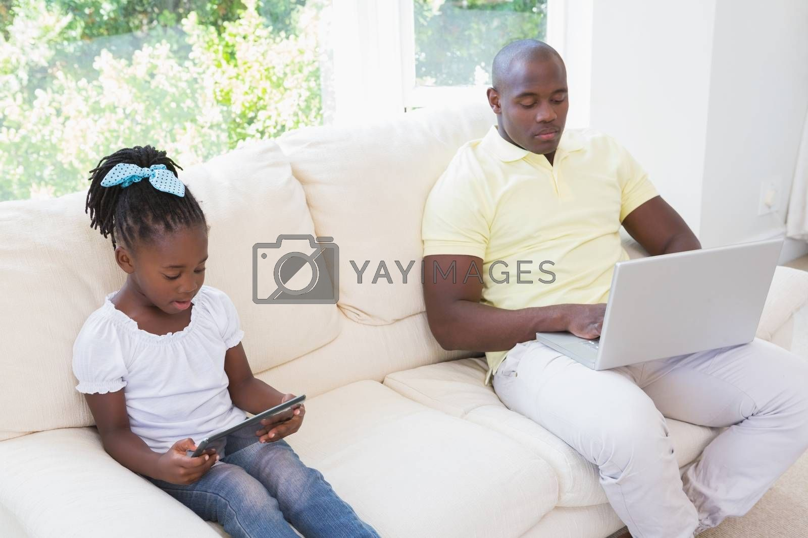 Royalty free image of Happy father using laptop and her daughter using tablet on couch  by Wavebreakmedia