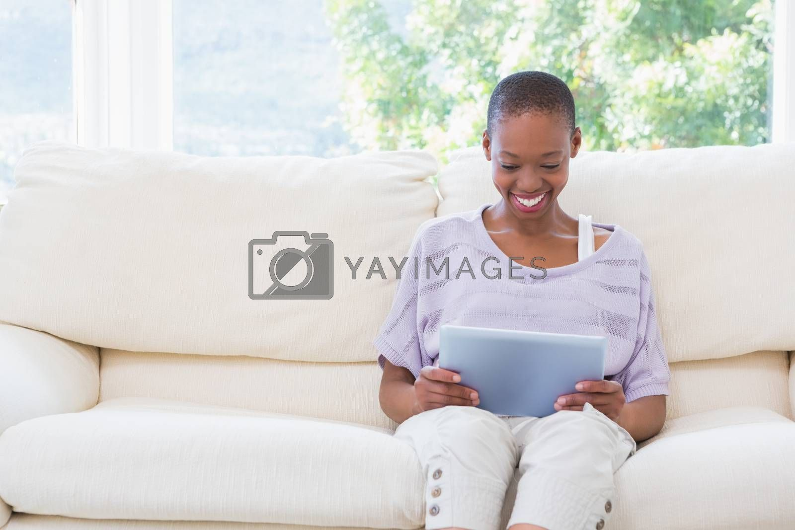 Royalty free image of Happy smiling woman using digital tablet on couch  by Wavebreakmedia