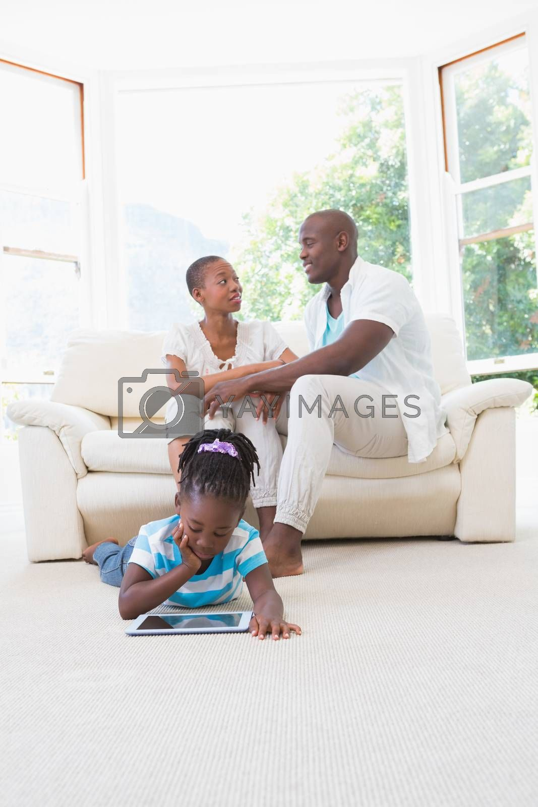 Royalty free image of Pretty couple sitting on couch and their daughter using digital tablet  by Wavebreakmedia