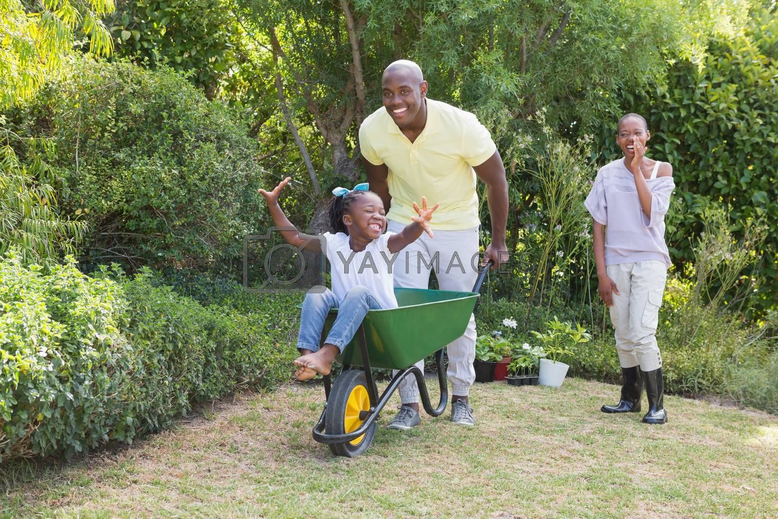Royalty free image of Happy smiling couple playing with wheelbarrow and their daughter  by Wavebreakmedia