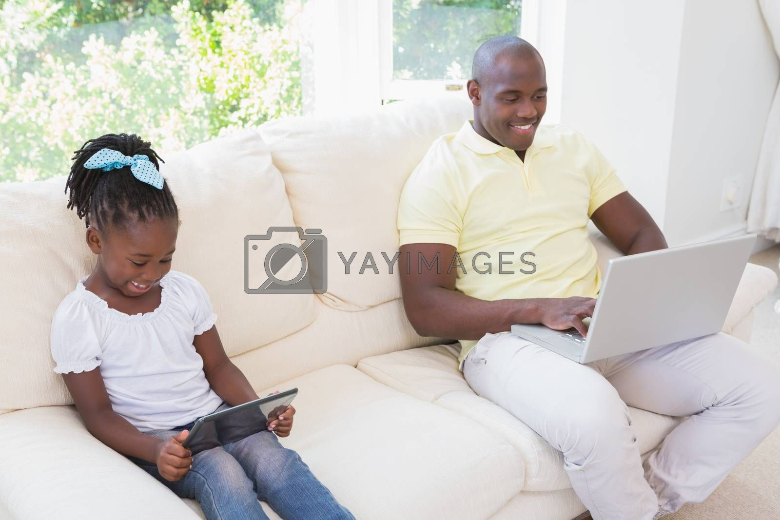 Royalty free image of Happy smiling father using laptop and her daughter using tablet on couch  by Wavebreakmedia