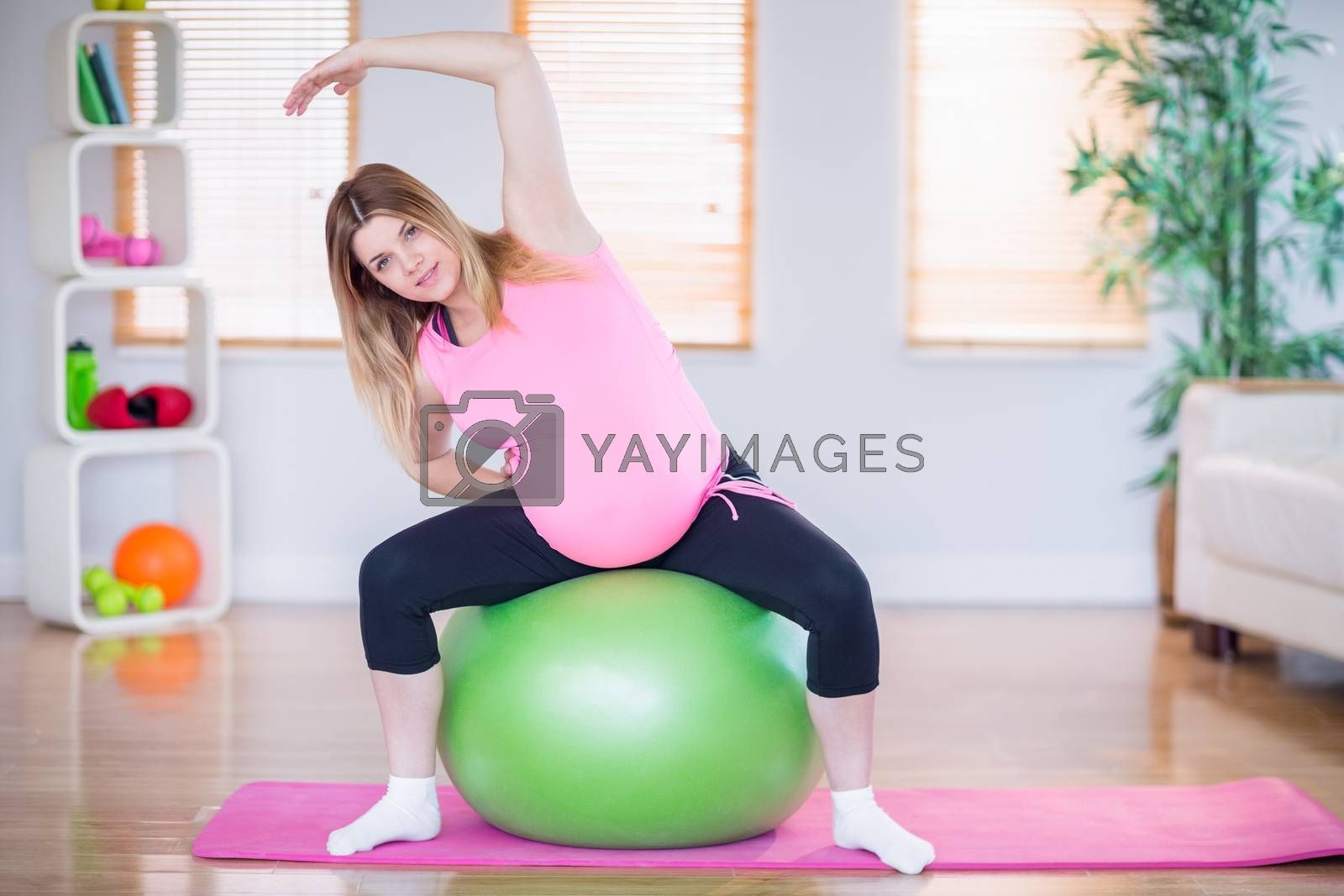 Royalty free image of Pregnant woman looking at camera sitting on exercise ball  by Wavebreakmedia