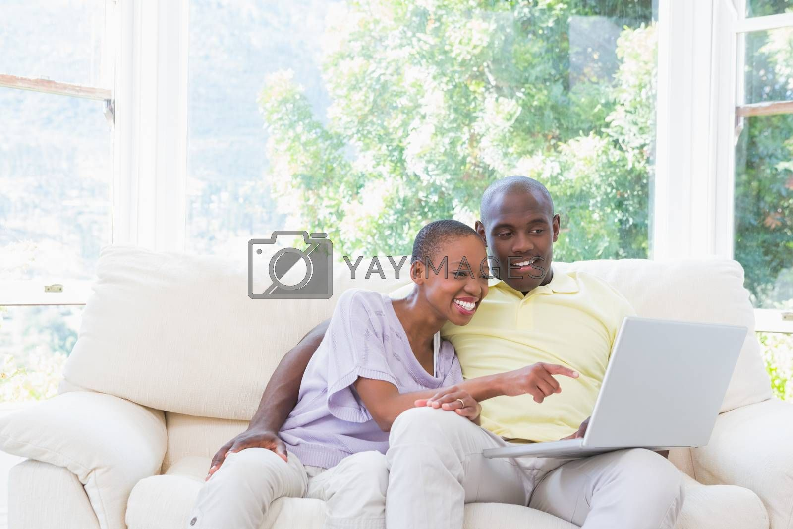 Royalty free image of Happy smiling couple using laptop on couch by Wavebreakmedia