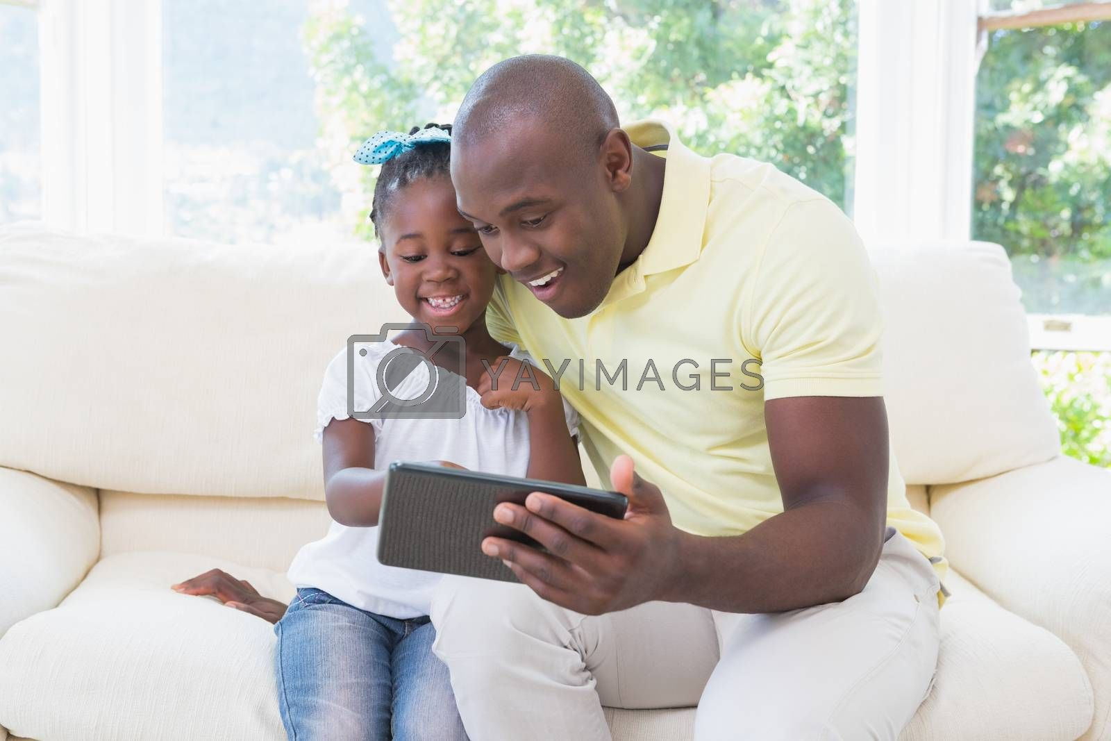 Royalty free image of Happy smiling father using digital tablet with her daughter on couch by Wavebreakmedia