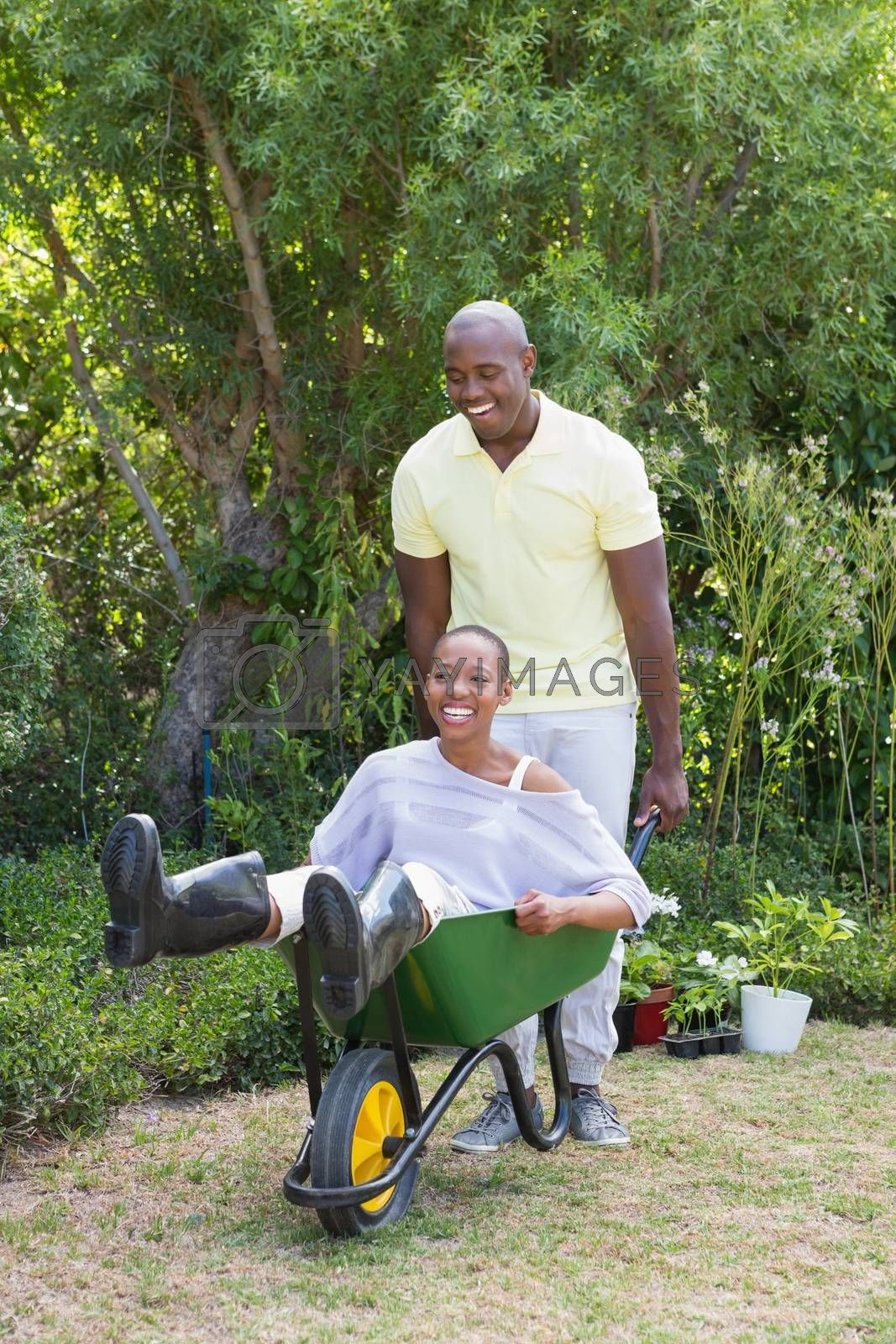 Royalty free image of Happy smiling couple playing with wheelbarrow  by Wavebreakmedia
