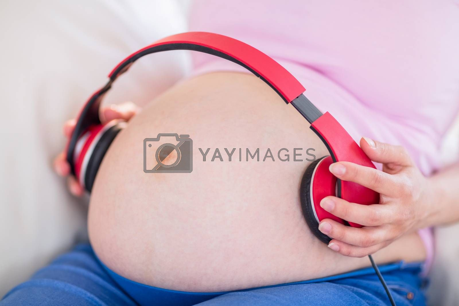 Royalty free image of Pregnant woman putting headphones on her belly by Wavebreakmedia