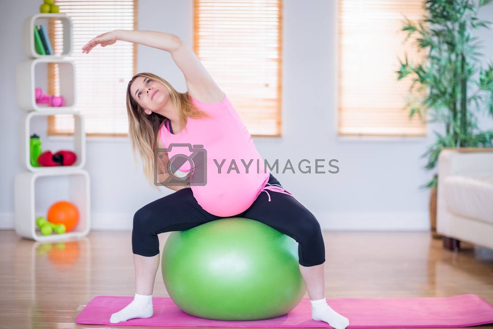 Royalty free image of Pregnant woman exercising on exercise ball by Wavebreakmedia