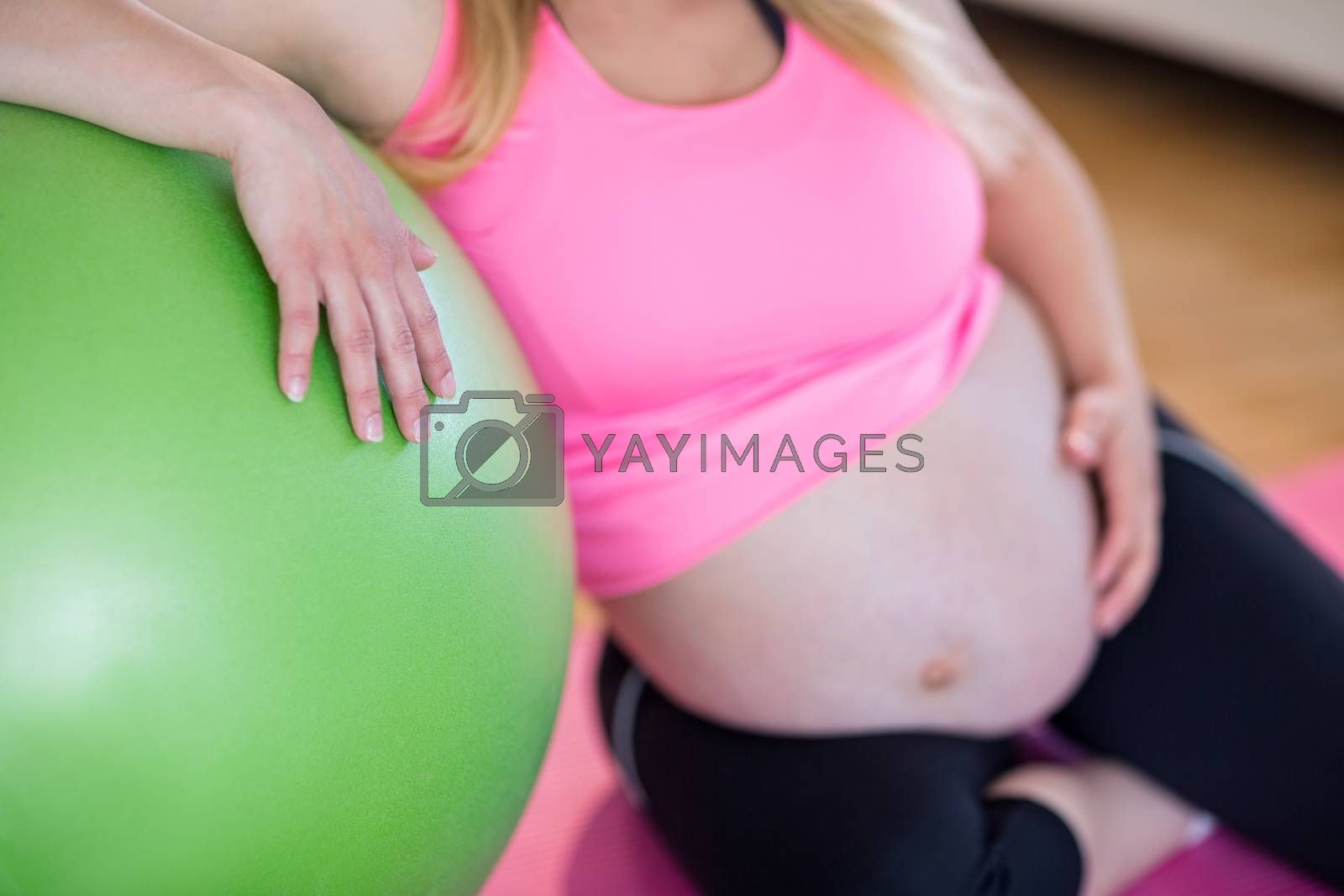 Royalty free image of Pregnant woman touching her belly next to exercise ball by Wavebreakmedia