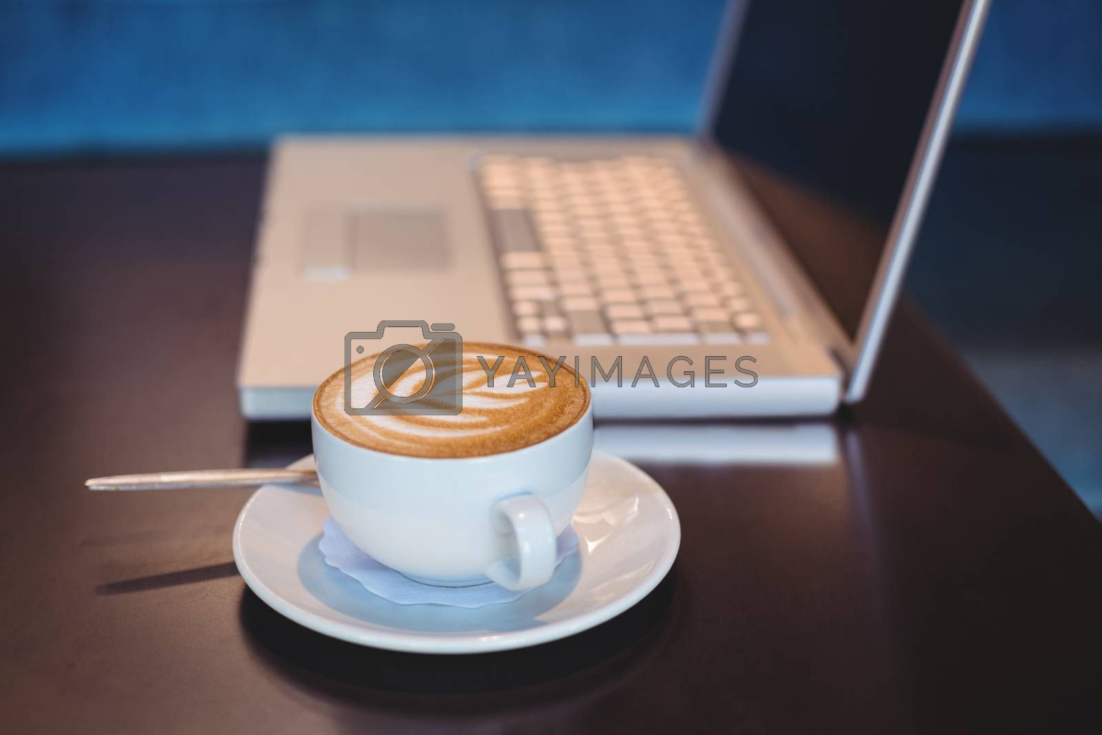 Royalty free image of Close-up of laptop and coffee on table by Wavebreakmedia