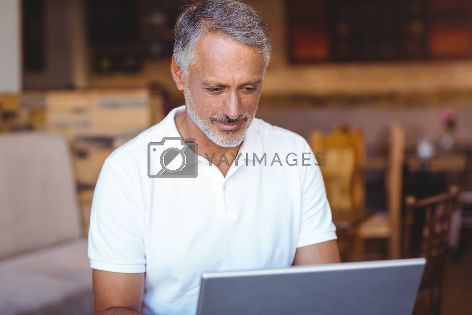 Royalty free image of Happy man using his laptop computer by Wavebreakmedia
