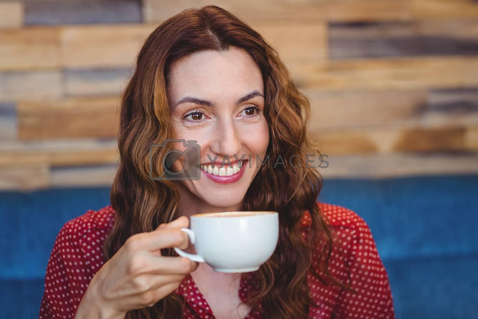 Royalty free image of Happy pretty brunette drinking coffee by Wavebreakmedia