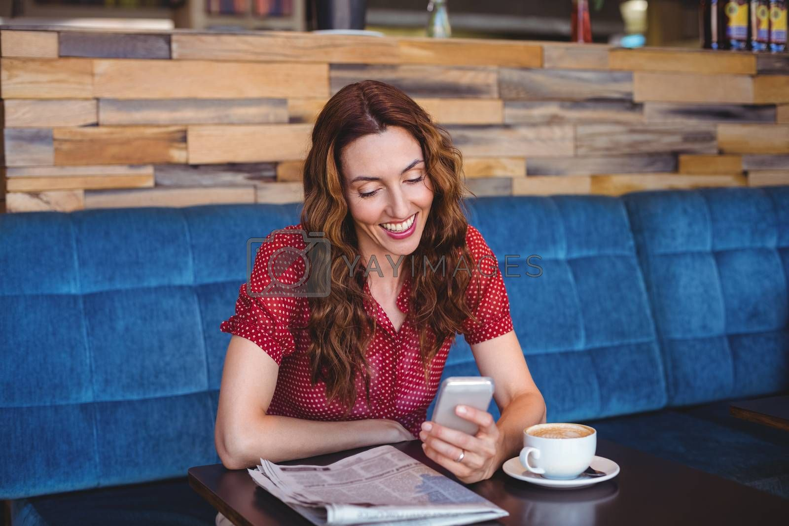 Royalty free image of Woman using her mobile phone and holding cup of coffee by Wavebreakmedia