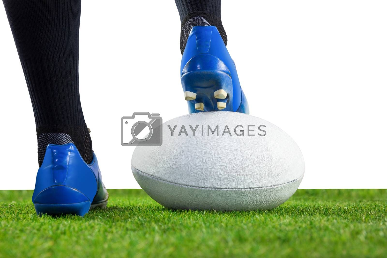 Royalty free image of Rugby player posing feet on the ball by Wavebreakmedia