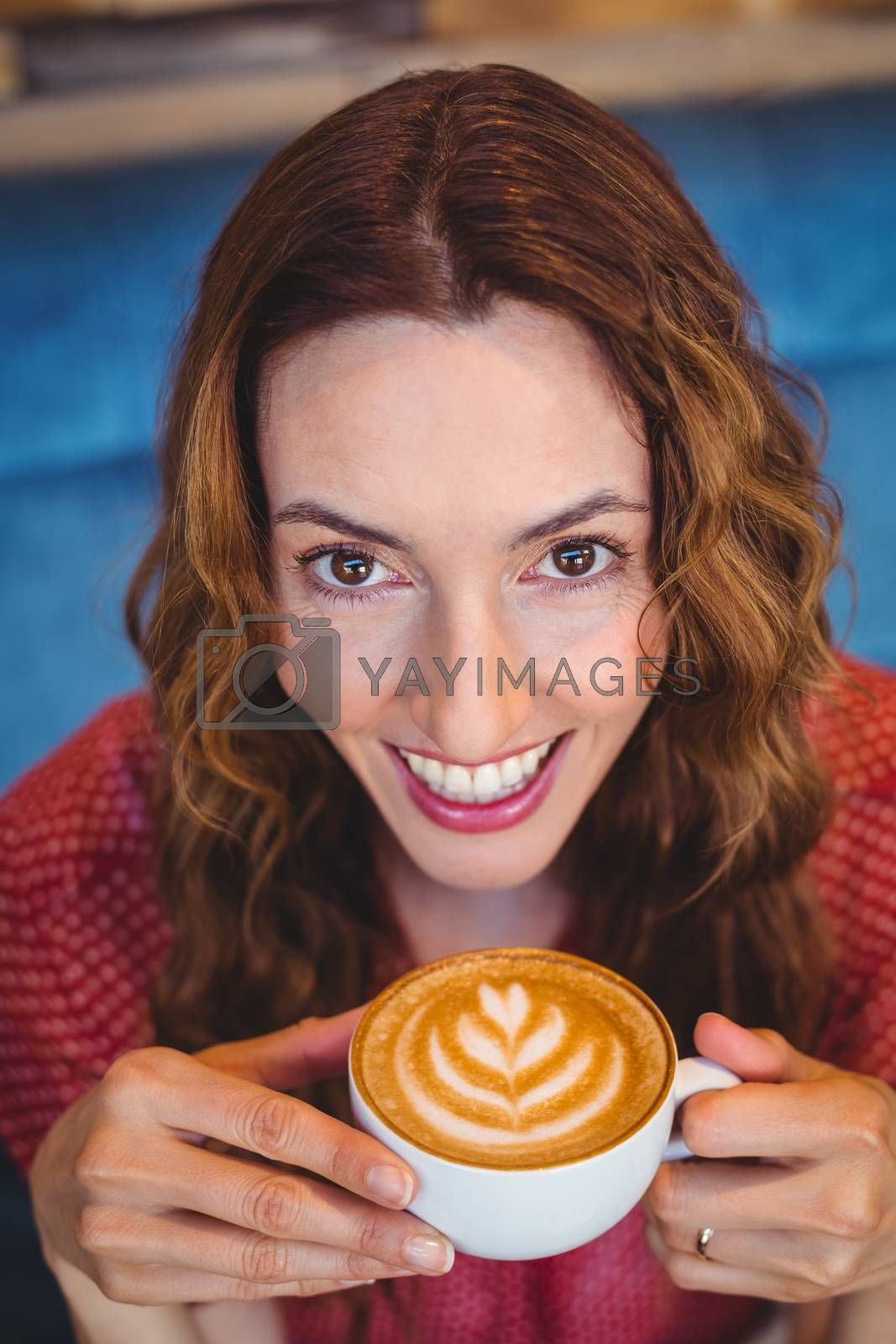 Royalty free image of Casual brunette drinking coffee by Wavebreakmedia
