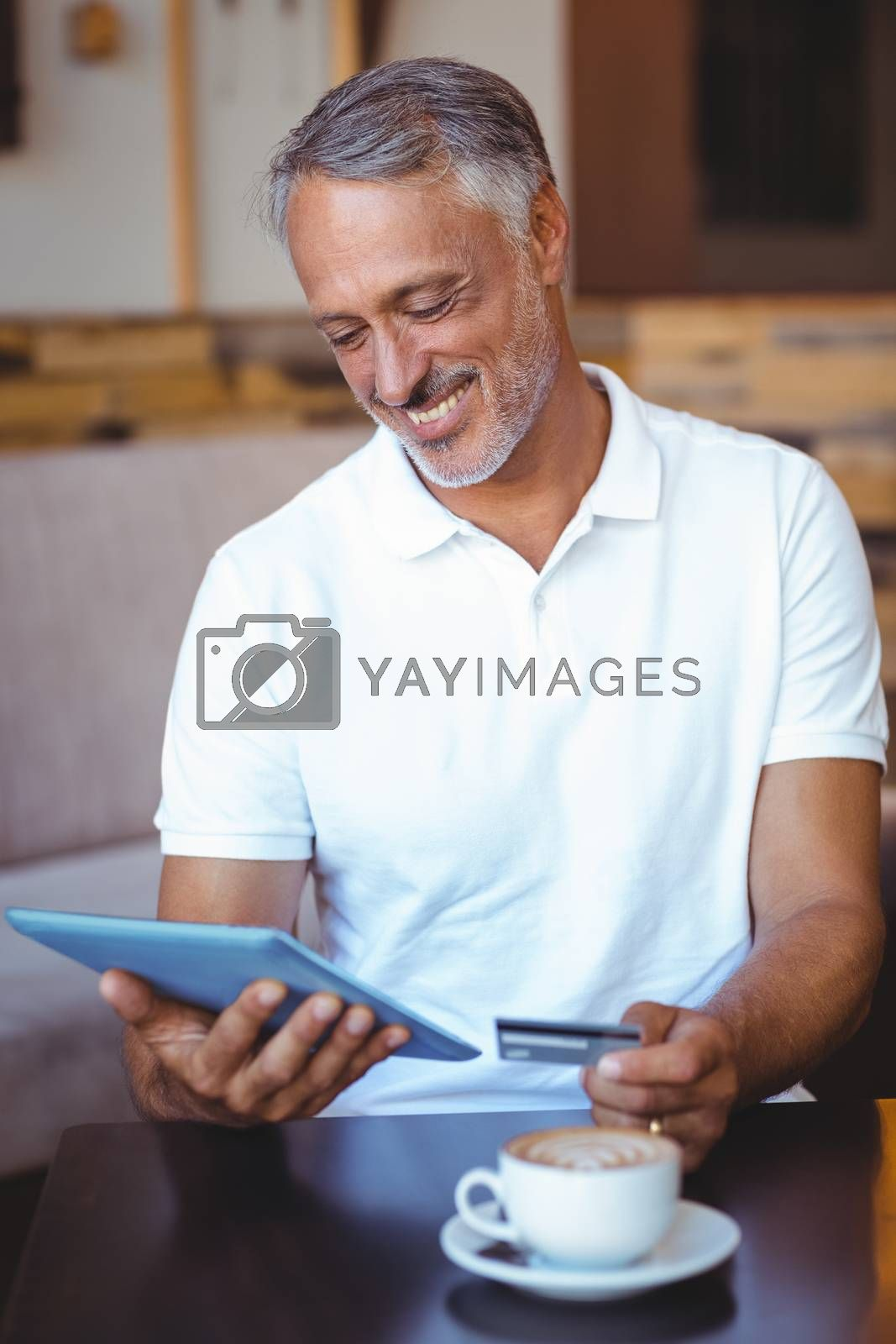 Royalty free image of a customer holding tablet and credit card by Wavebreakmedia