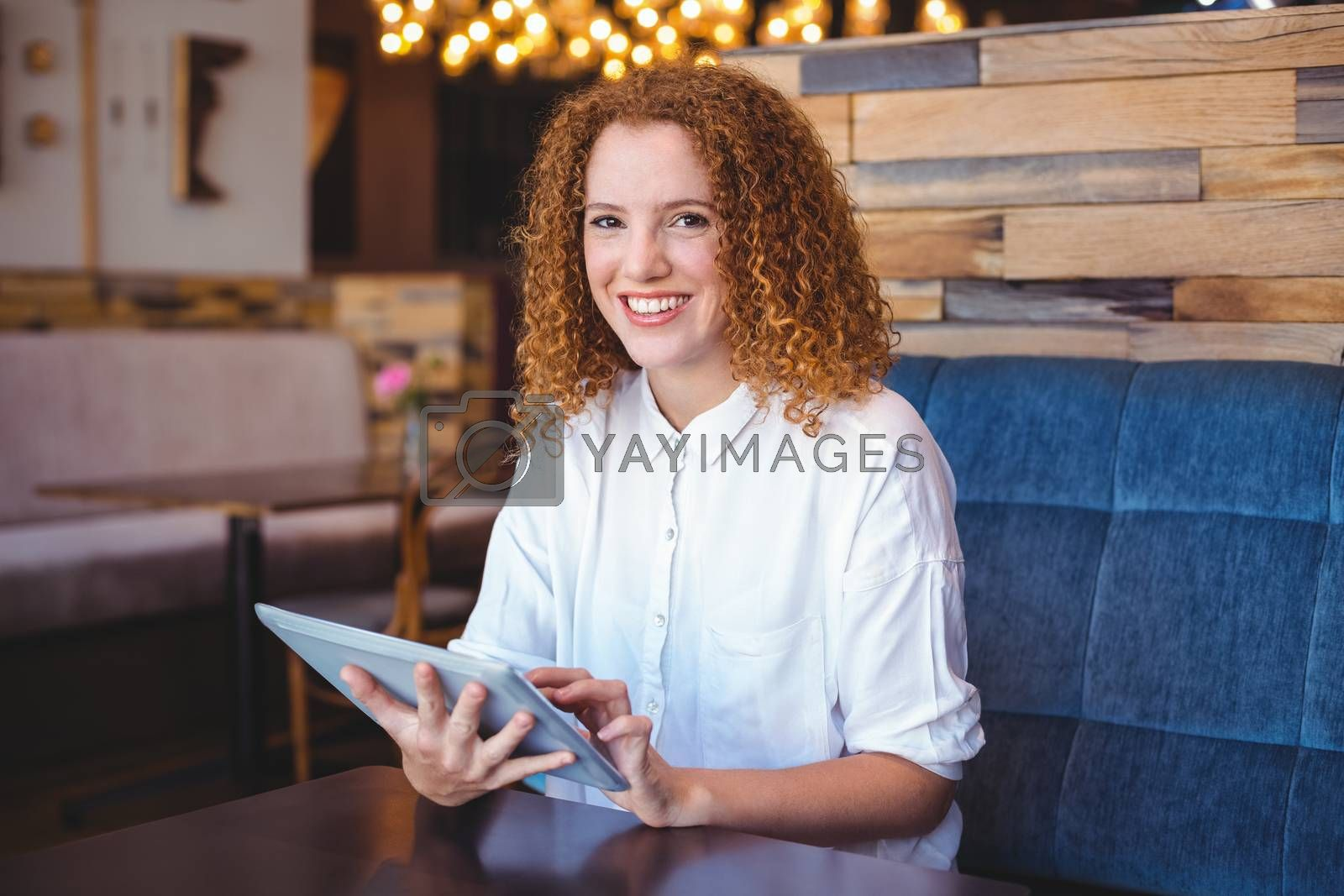 Royalty free image of Pretty girl using a small tablet at table by Wavebreakmedia