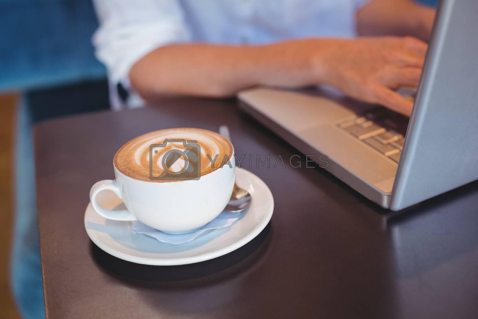 Royalty free image of Pretty girl having coffee using laptop by Wavebreakmedia