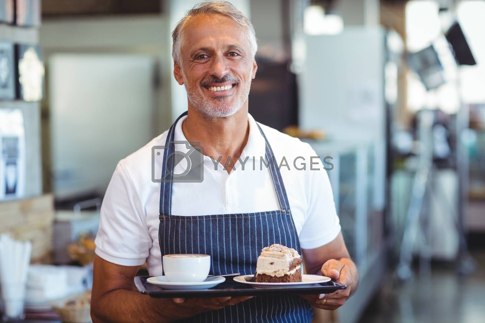 Royalty free image of waiter smiling and holding tray by Wavebreakmedia
