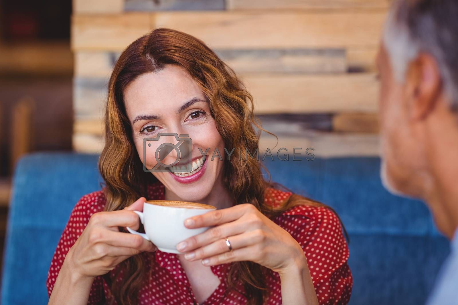 Royalty free image of Cute couple having coffee together  by Wavebreakmedia