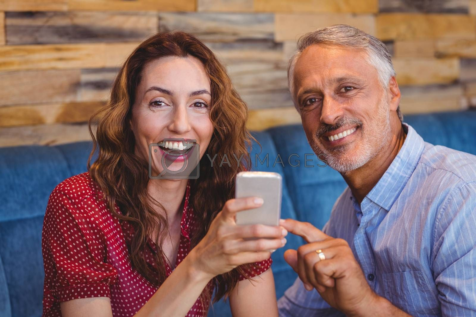 Royalty free image of cute couple looking at their phones by Wavebreakmedia