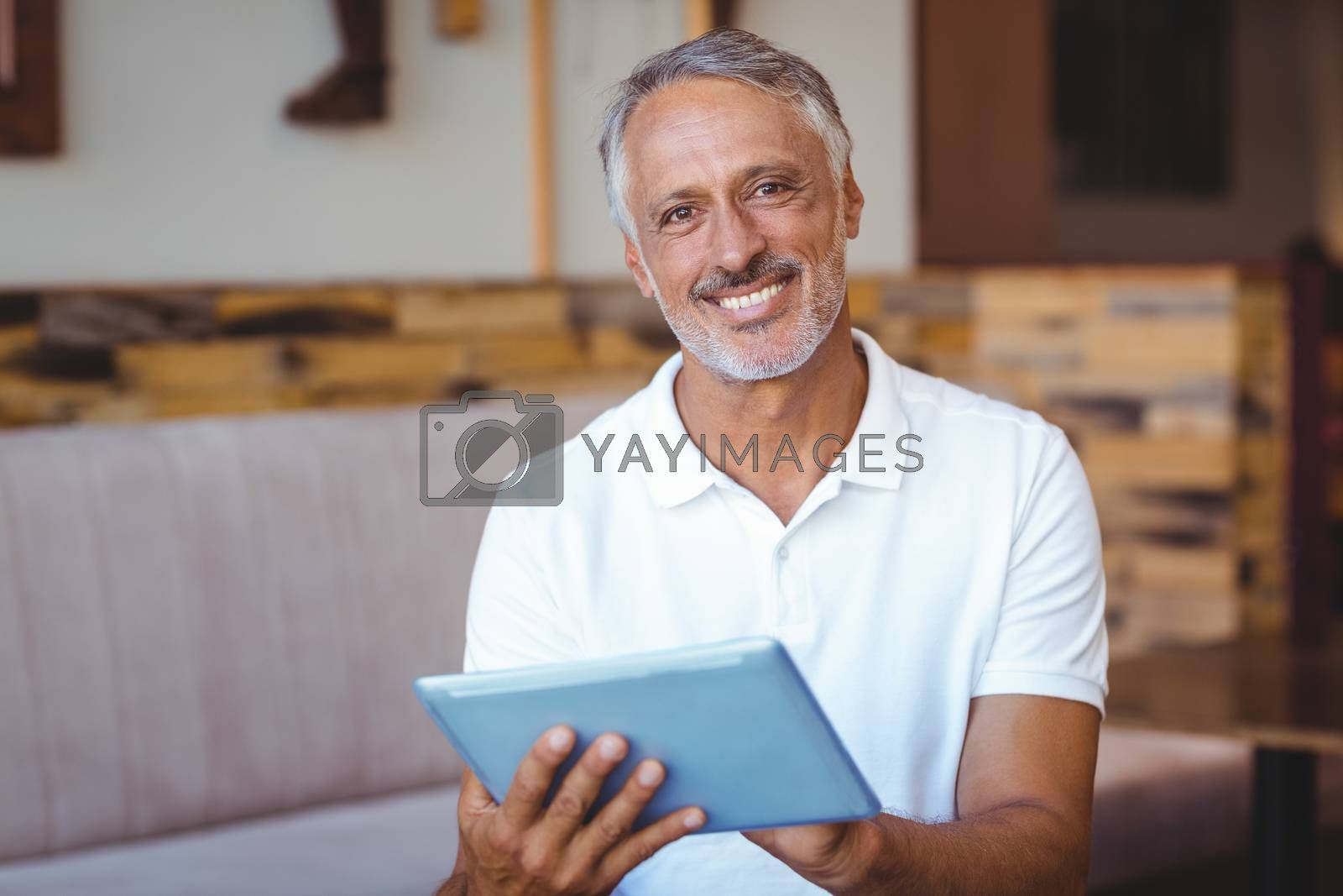 Royalty free image of Casual man using his tablet by Wavebreakmedia