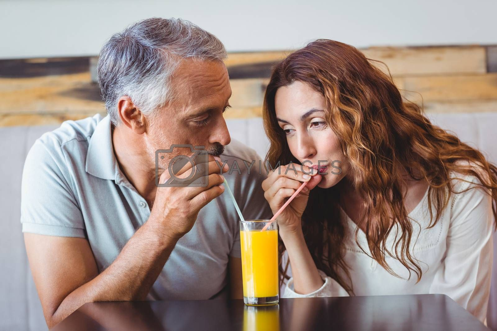Royalty free image of cute couple having glass of orange juice by Wavebreakmedia
