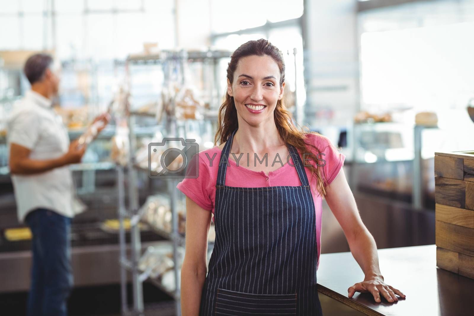 Royalty free image of Pretty waitress leaning on counter by Wavebreakmedia