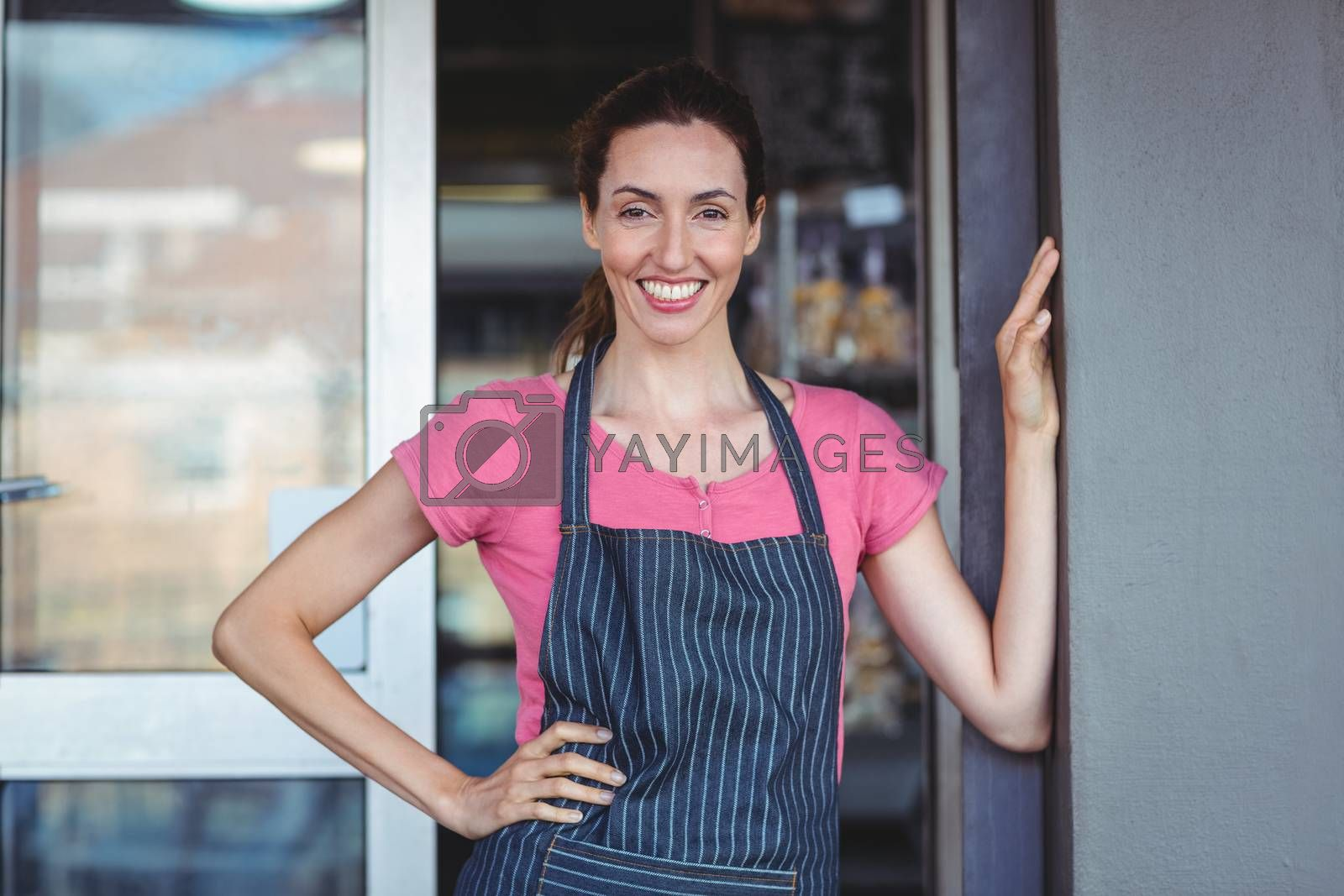 Royalty free image of Pretty waitress leaning on the wall by Wavebreakmedia