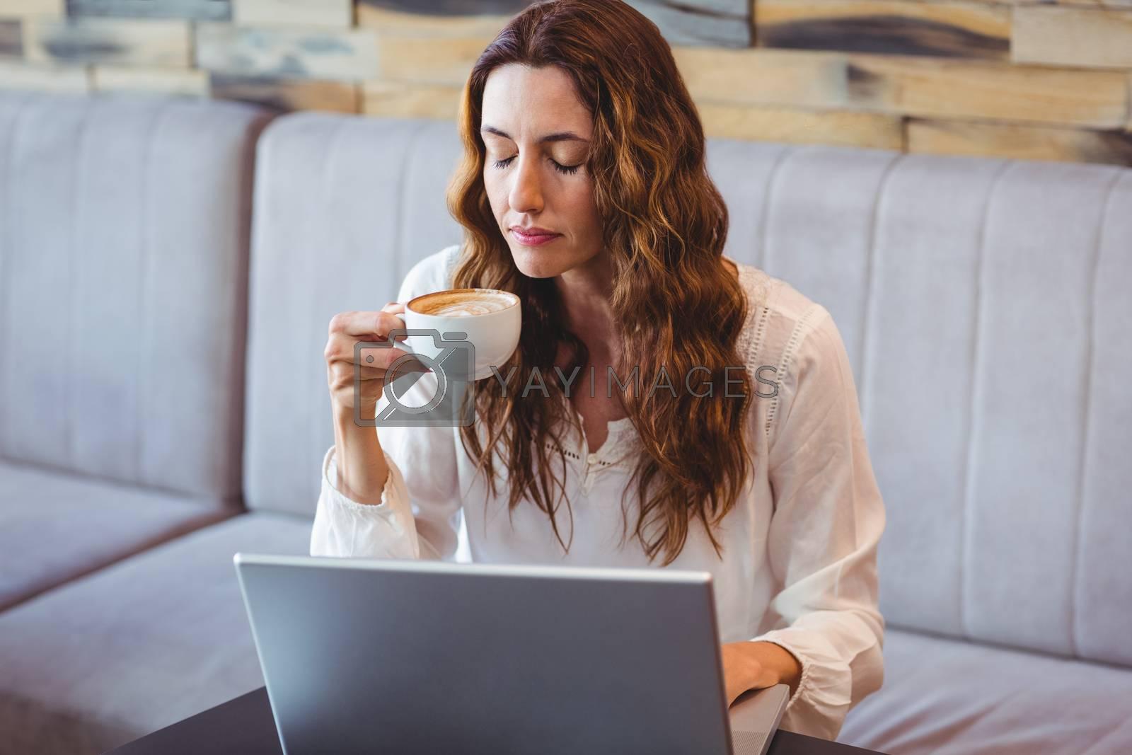 Royalty free image of Pretty brunette having coffee using laptop by Wavebreakmedia