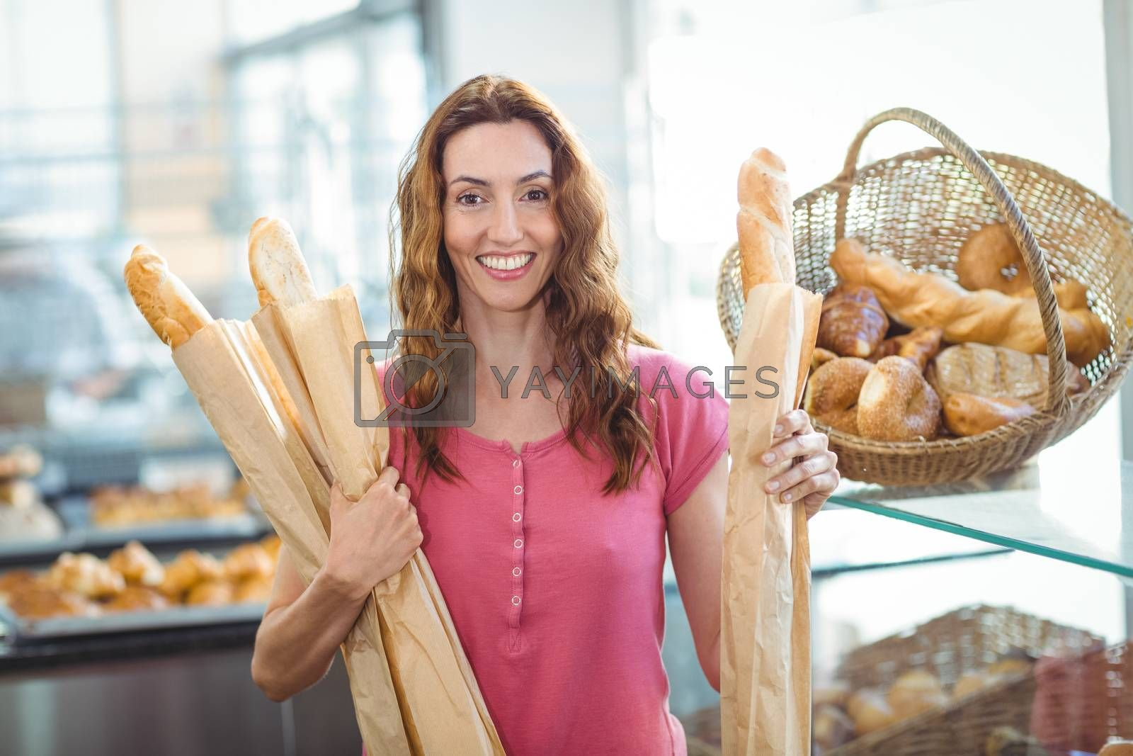 Royalty free image of Pretty brunette holding baguettes by Wavebreakmedia