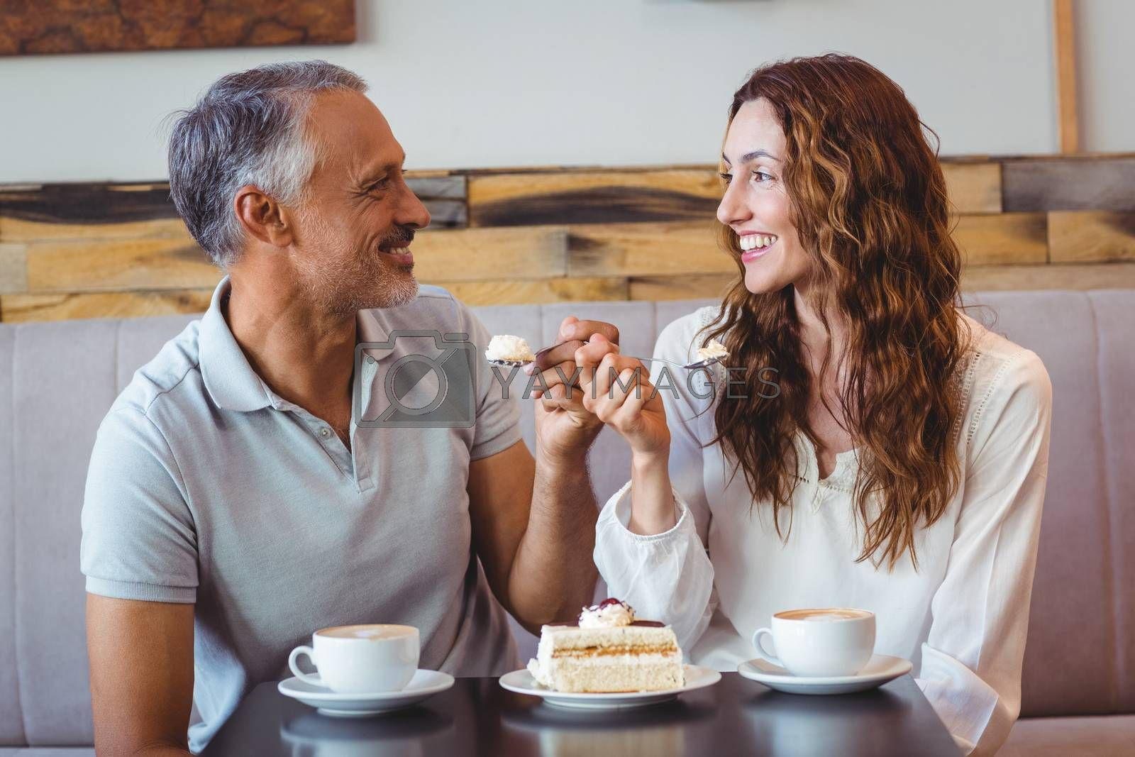 Royalty free image of Casual couple having coffee and cake together by Wavebreakmedia