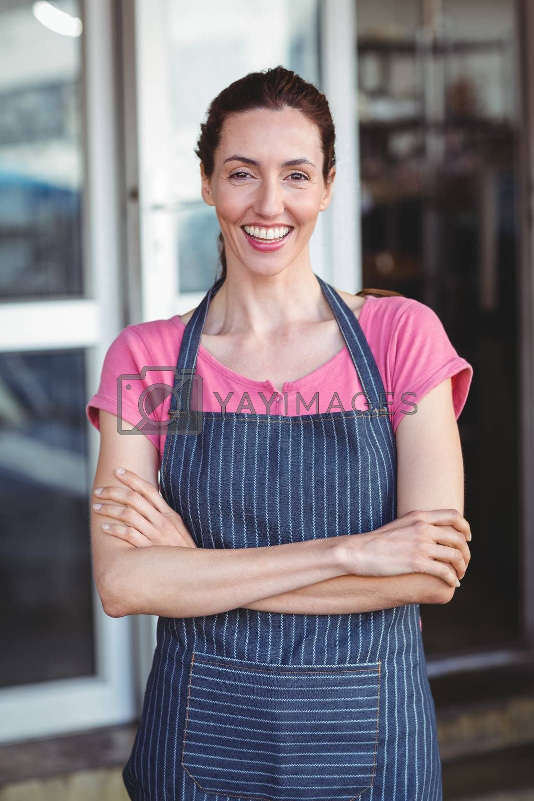 Royalty free image of Smiling worker looking at camera with arm crossed by Wavebreakmedia