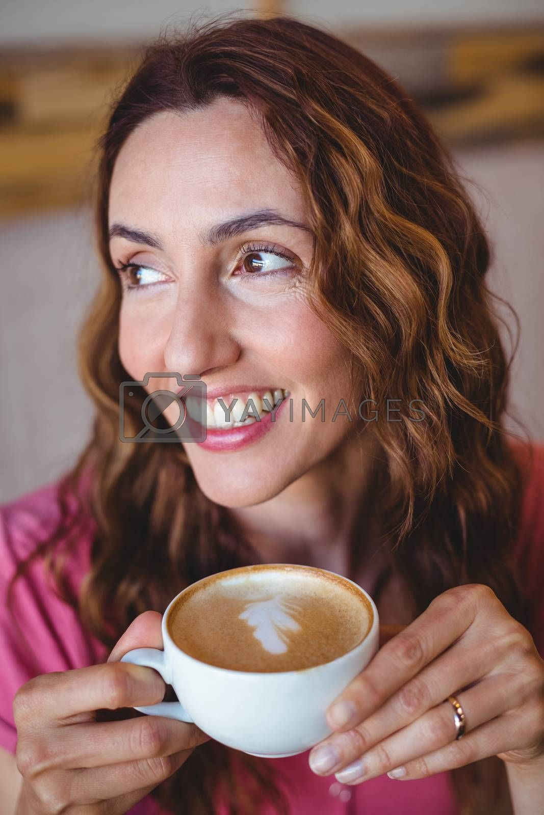 Royalty free image of Pretty brunette having cup of coffee by Wavebreakmedia
