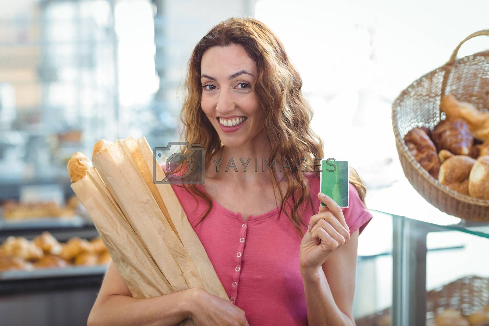 Royalty free image of Pretty brunette holding credit card and baguettes by Wavebreakmedia