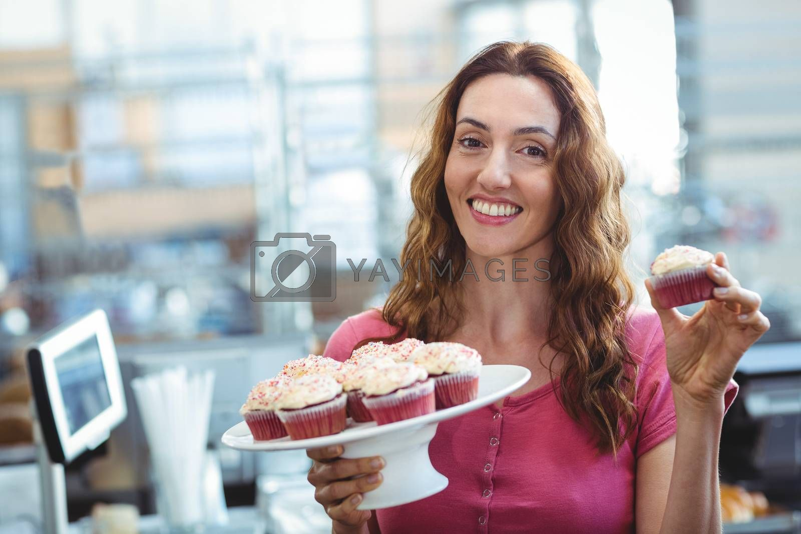 Royalty free image of Pretty brunette showing cupcake  by Wavebreakmedia