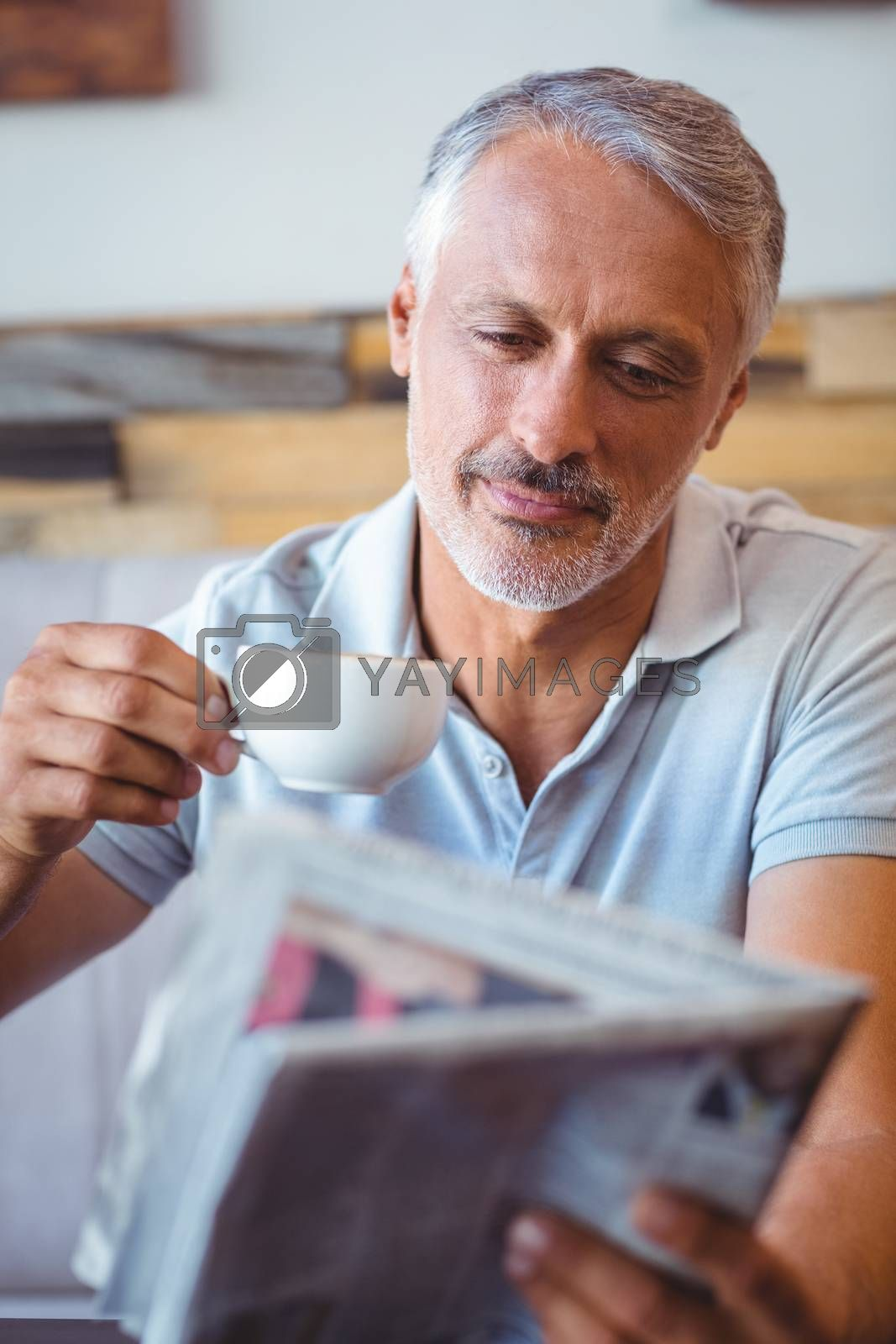 Royalty free image of Smiling man having cup of coffee reading newspaper by Wavebreakmedia