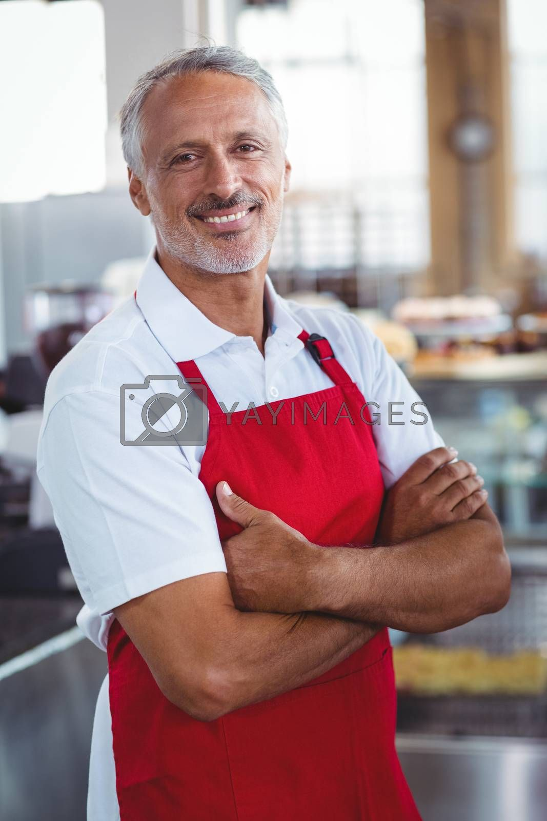 Royalty free image of Happy barista smiling at camera with arms crossed by Wavebreakmedia