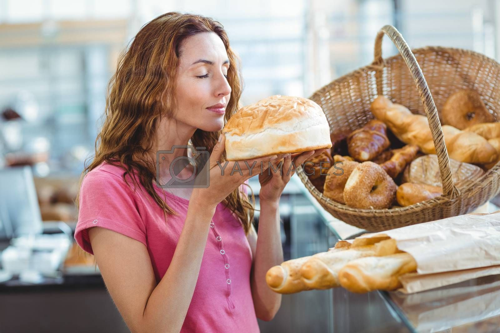 Royalty free image of Pretty brunette smelling loaf of bread by Wavebreakmedia