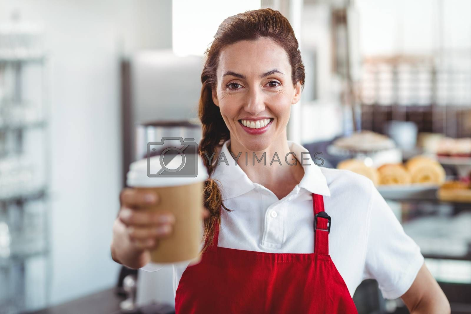 Royalty free image of Pretty barista giving take-away cup by Wavebreakmedia
