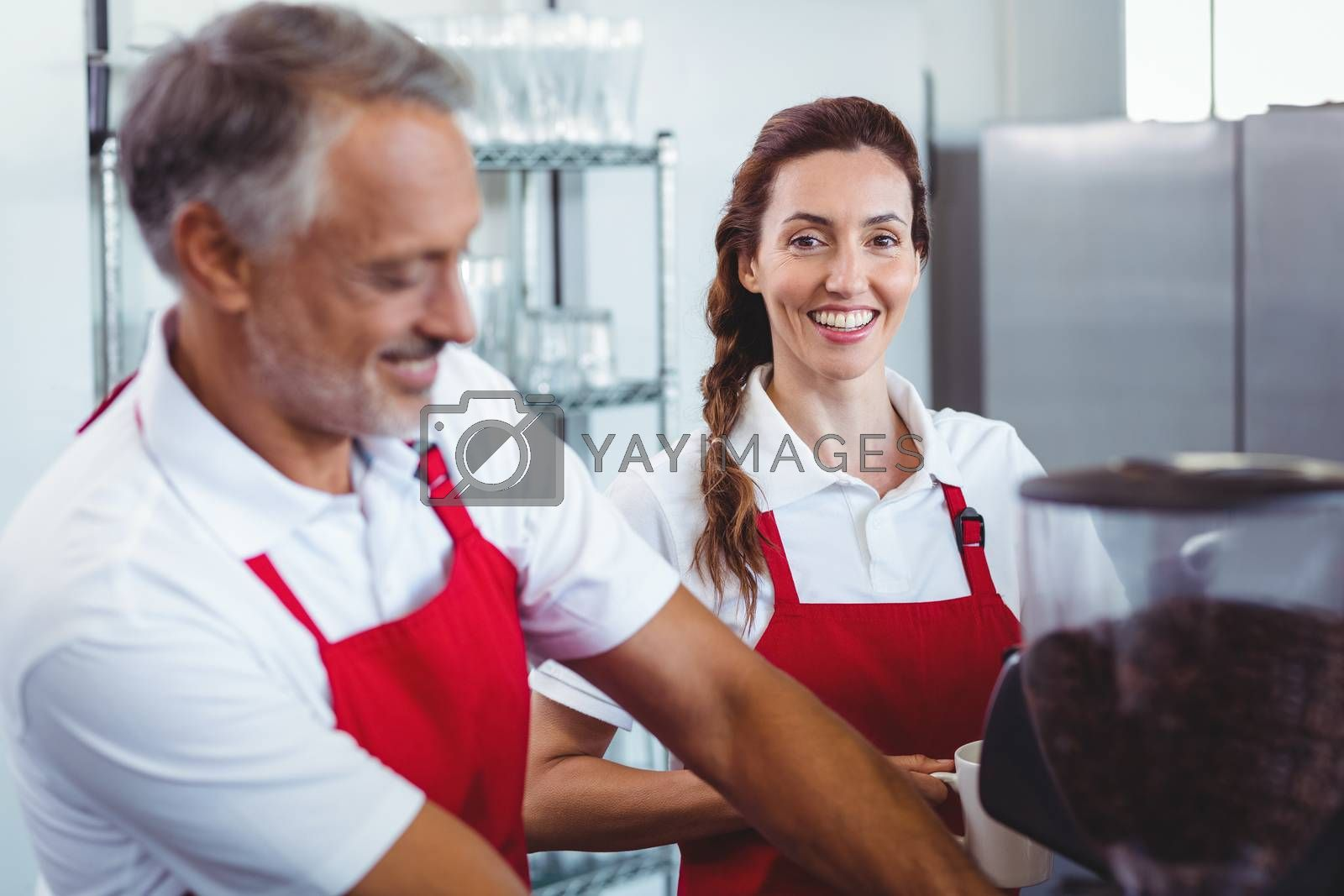 Royalty free image of Pretty barista looking at camera and holding a mug of coffee by Wavebreakmedia