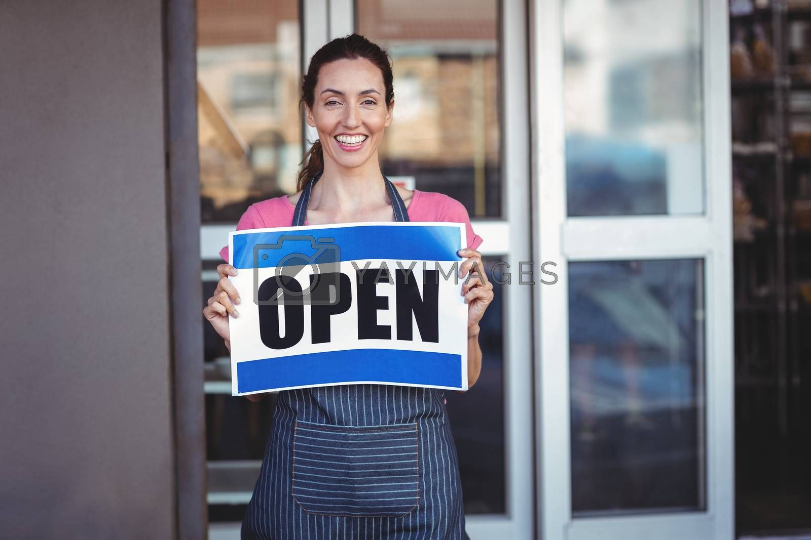Royalty free image of Pretty worker showing open sign by Wavebreakmedia