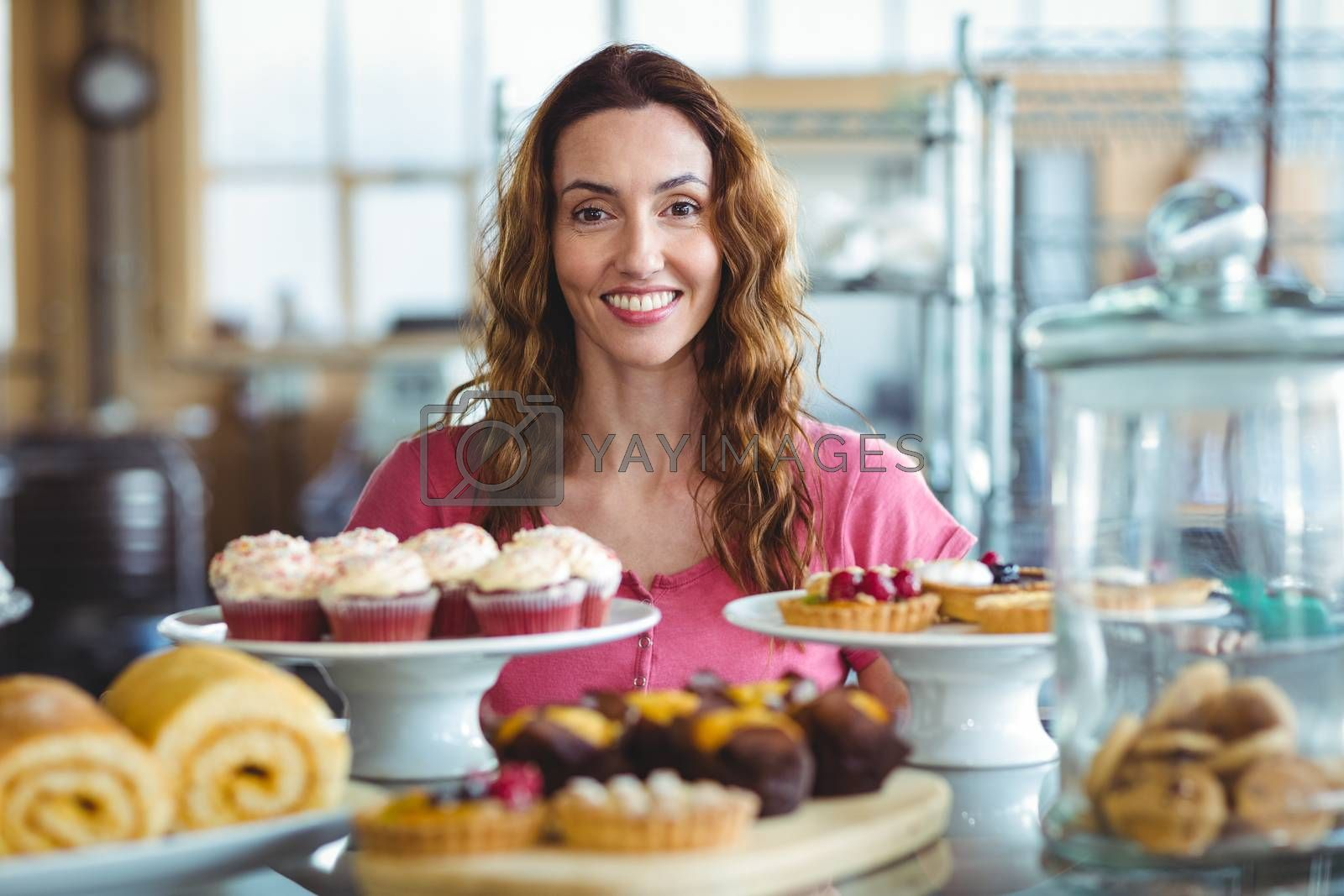 Royalty free image of Pretty brunette smiling at camera behind counter by Wavebreakmedia