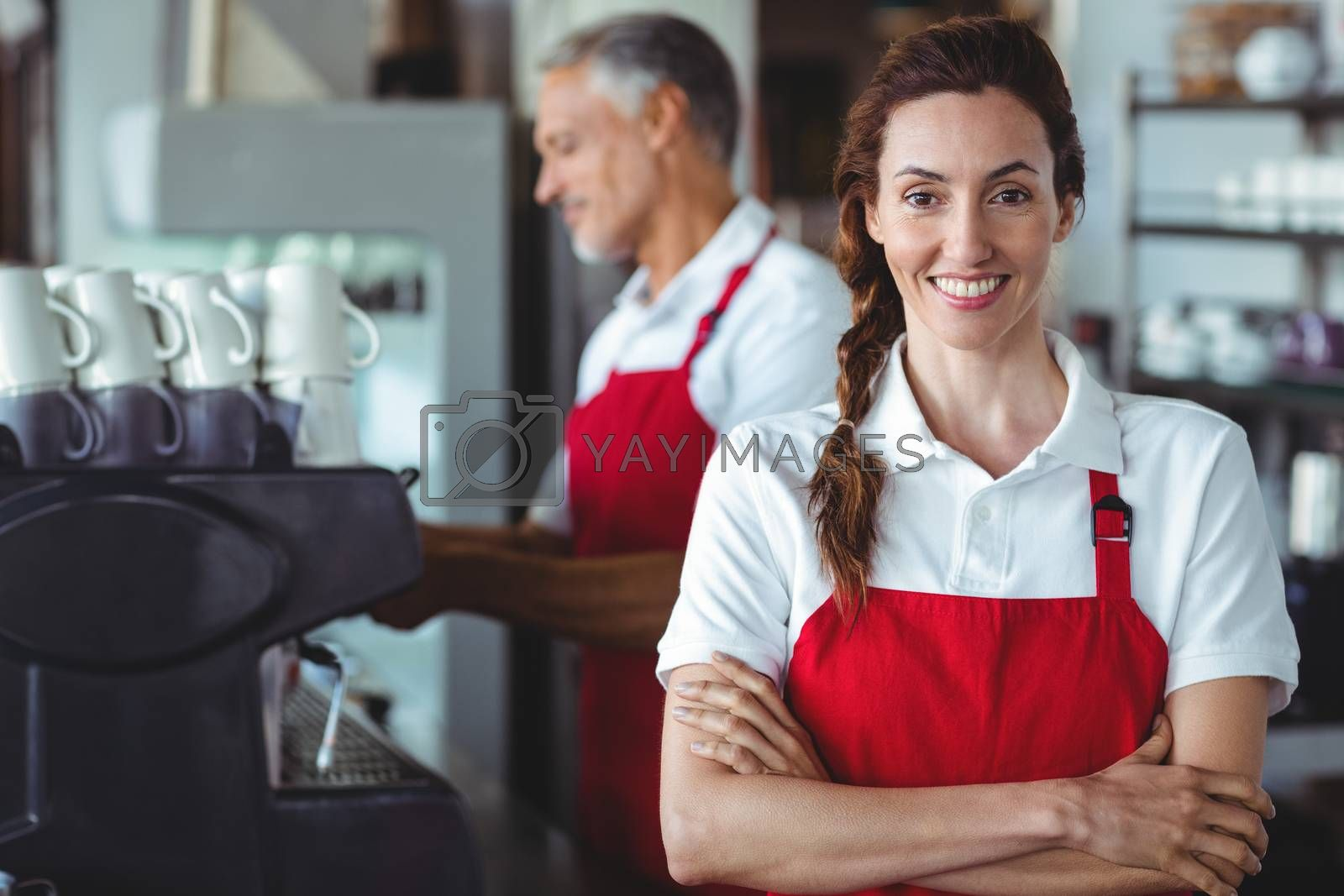 Royalty free image of Pretty barista smiling at camera with colleague behind by Wavebreakmedia