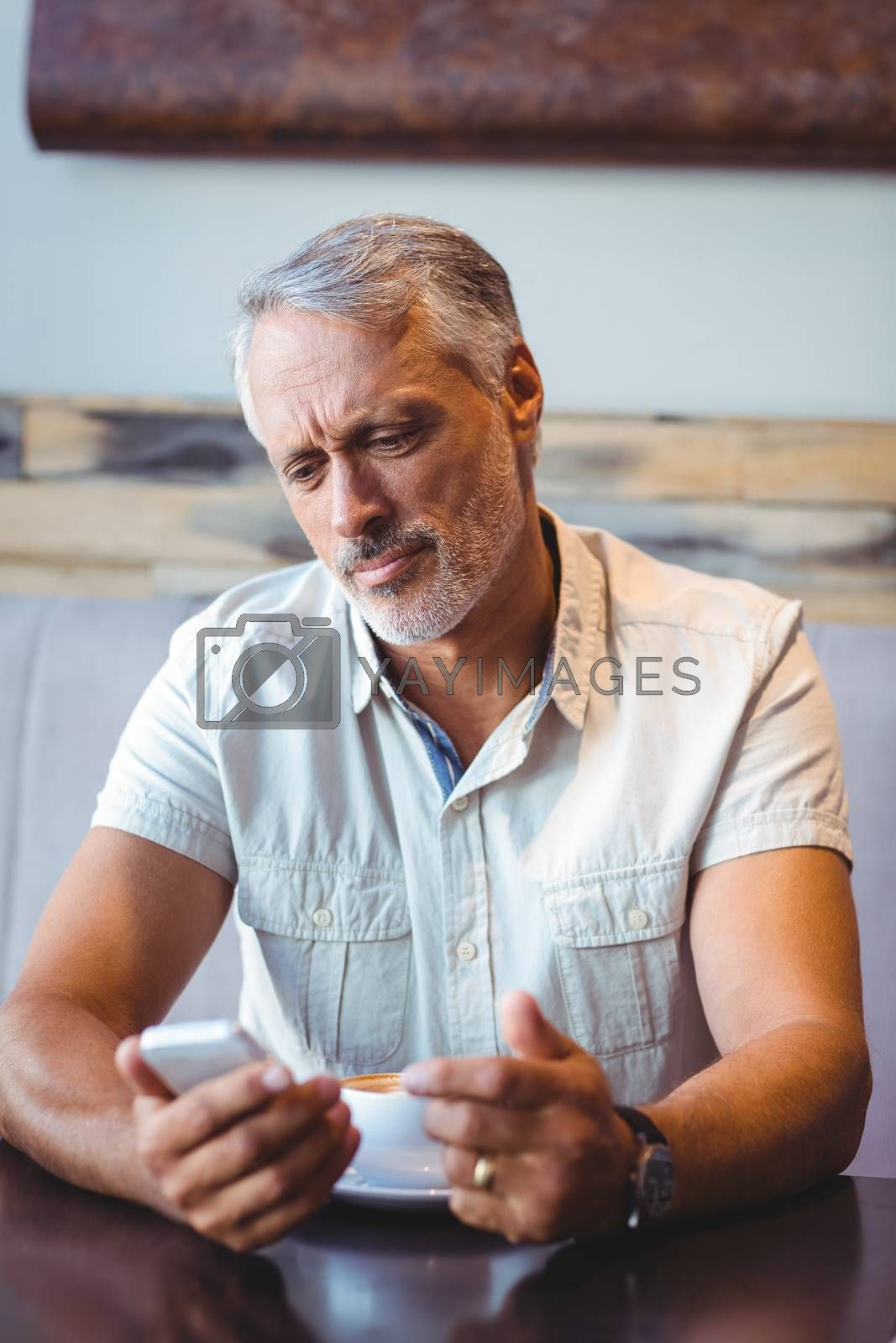 Royalty free image of Casual man using mobile phone in coffee shop by Wavebreakmedia