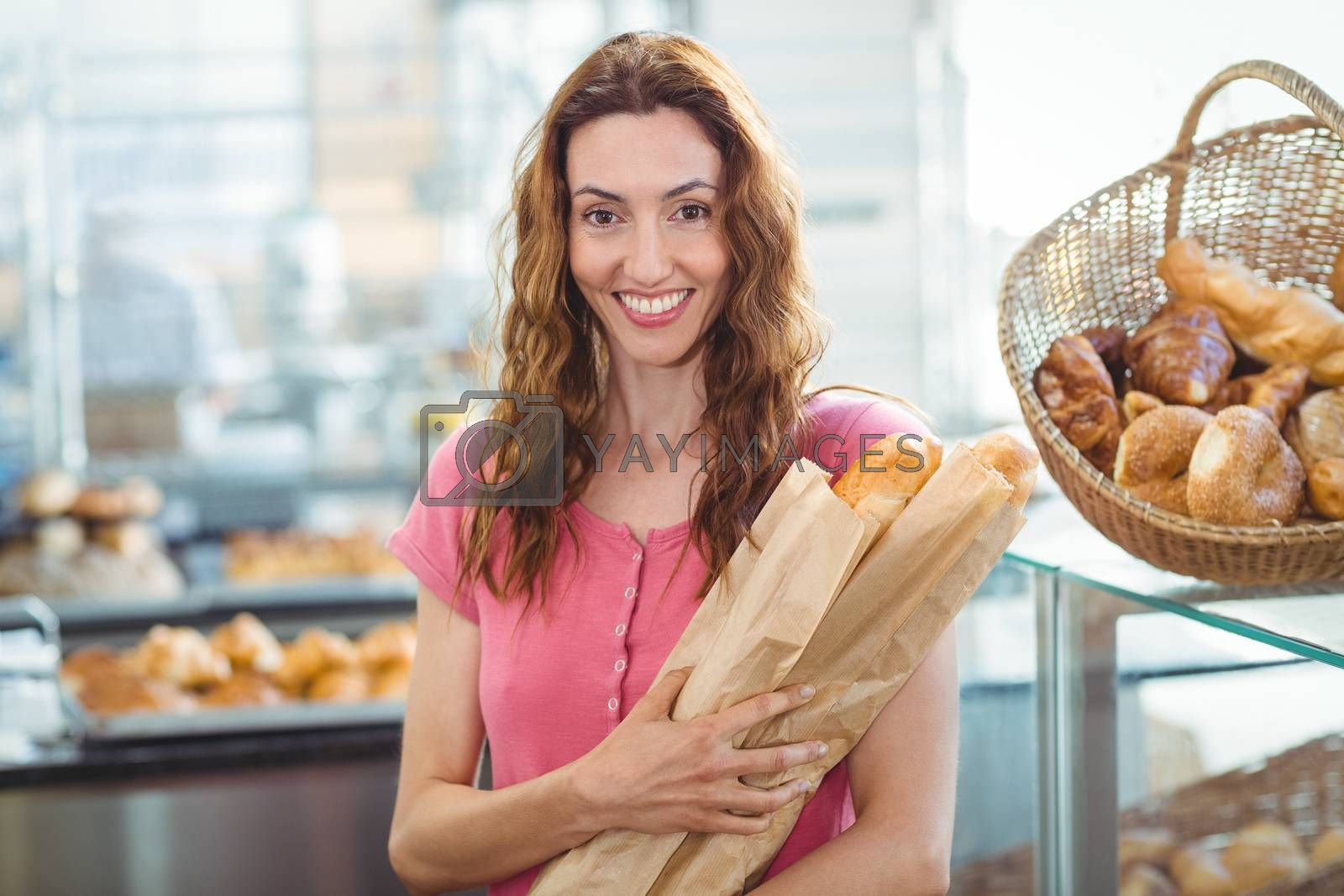 Royalty free image of Smiling young brunette with baguettes by Wavebreakmedia