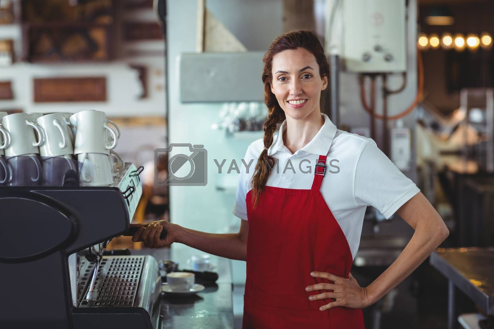 Royalty free image of Pretty barista looking at camera and using the coffee machine by Wavebreakmedia