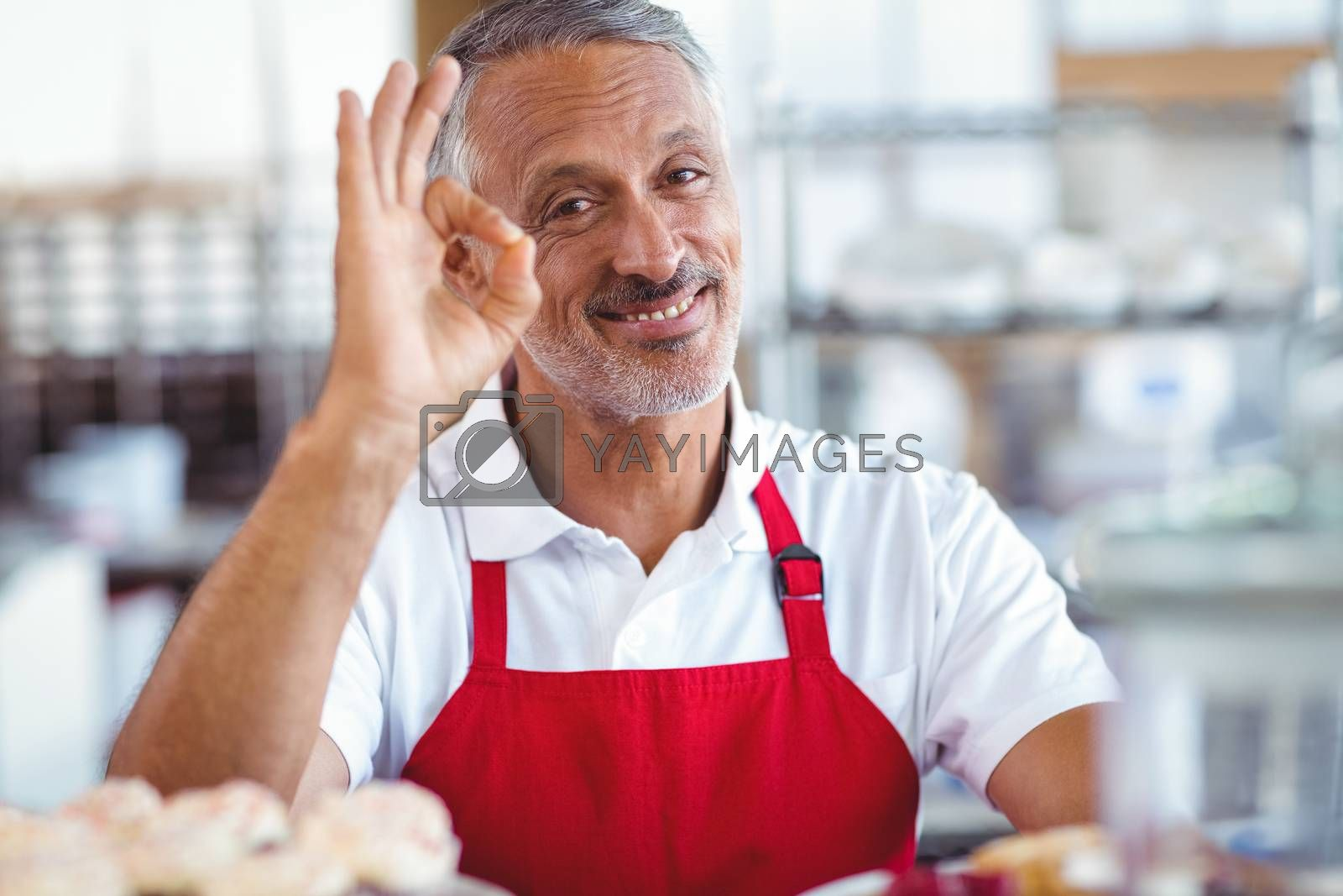 Royalty free image of Happy barista looking at camera and gesturing ok sign  by Wavebreakmedia