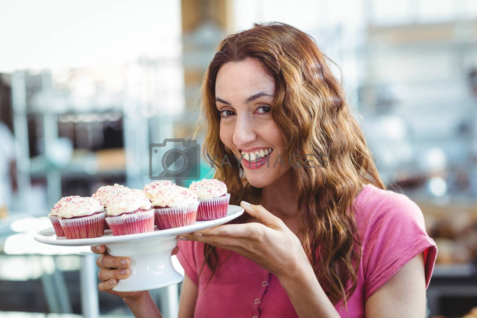 Royalty free image of Pretty brunette holding plate of pastries by Wavebreakmedia