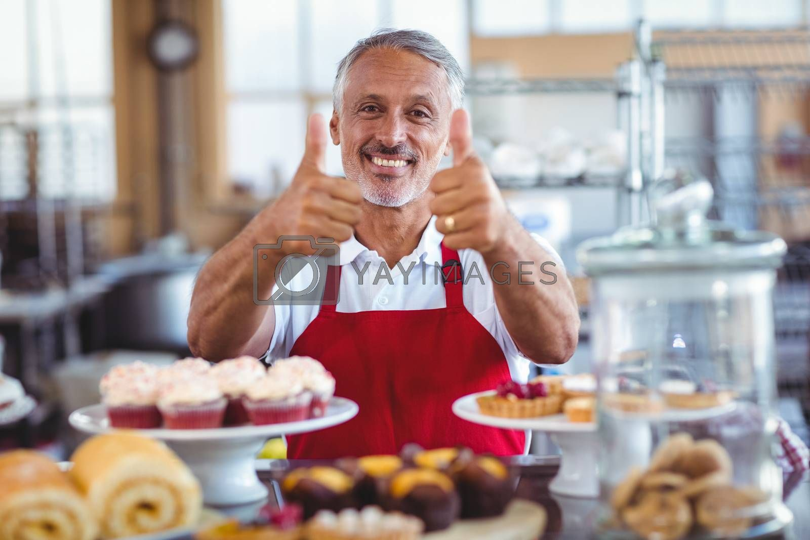 Royalty free image of Happy barista looking at camera and gesturing thumbs up by Wavebreakmedia
