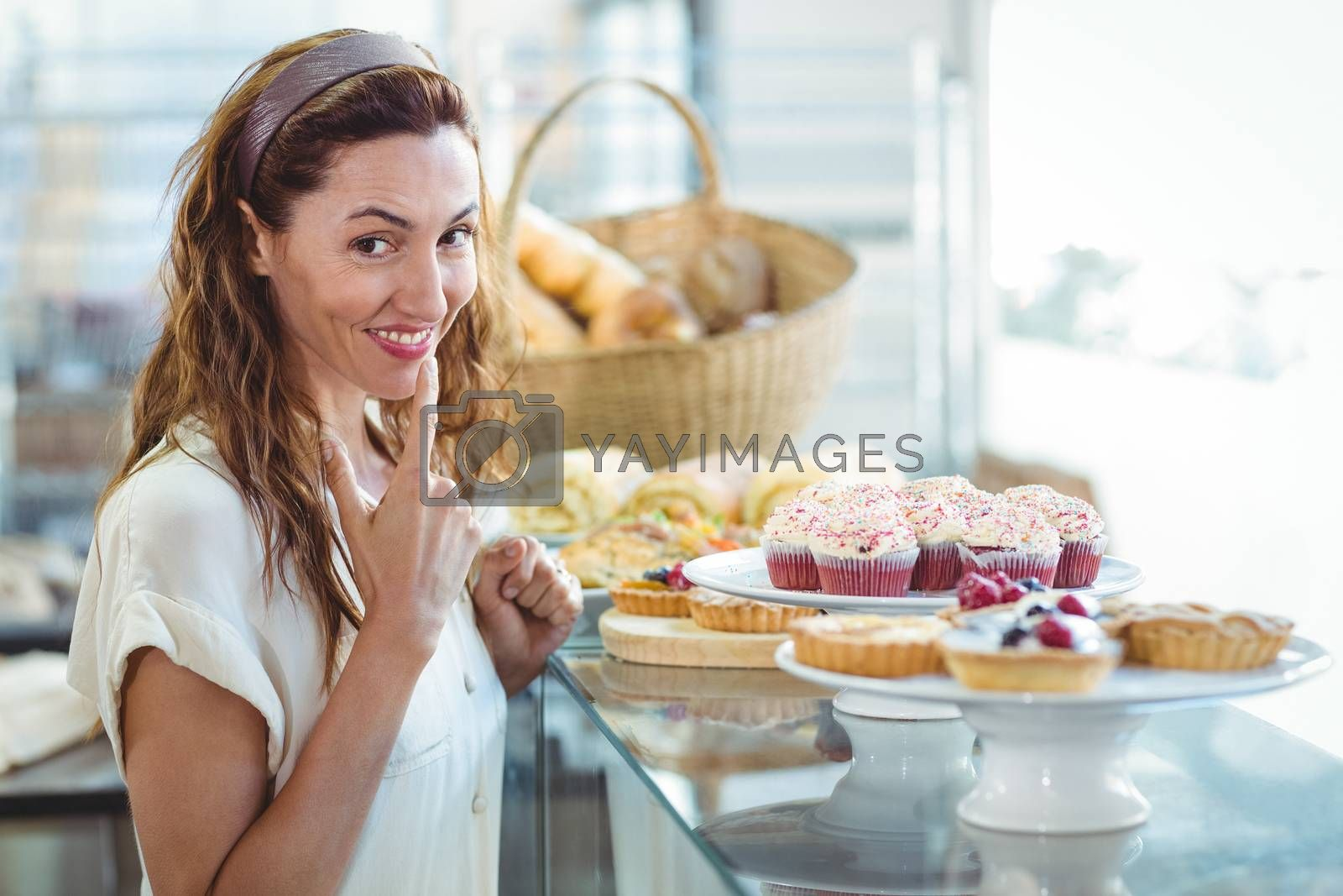 Royalty free image of Hesitating pretty woman looking at camera by Wavebreakmedia